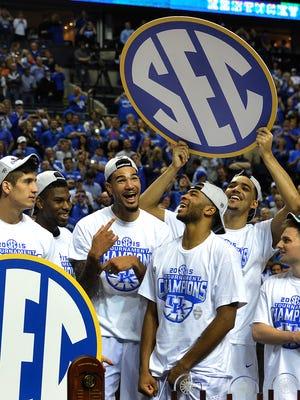 Kentucky players celebrate after beating Arkansas 78-63 to win the SEC Men's Basketball championship game on Sunday at Bridgestone Arena.