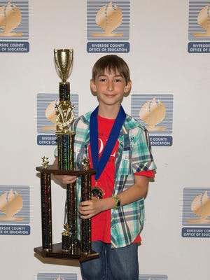 Fifth grader Vincent Parsy proudly displays his sweepstakes trophy at the Riverside County science fair. Parsy won a gold medal for his project and won the overall elementary division.