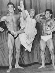 British Actress Vera Day swings on the muscle packed arms of Mickey Hargitay (Left) the 1955 amateur Mr. Universe and Leo Roberts professional Mr. Universe for 1955.
