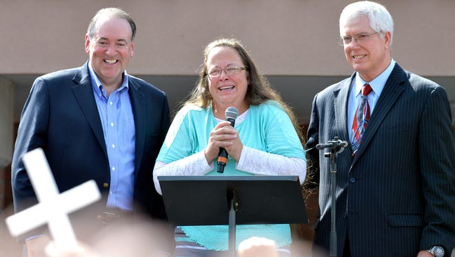 Rowan County Clerk Kim Davis, center with Republican presidential candidate Mike Huckabee, left, and attorney Mat Staver, right, founder of the Liberty Counsel, the Christian law firm representing Davis, at her side, greets the crowd after being released from the Carter County Detention Center, Tuesday,