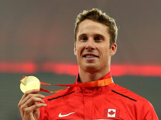Derek Drouin poses with his gold after winning the Men's High Jump final during the IAAF World Athletics Championships, Aug. 30, 2015 in Beijing.