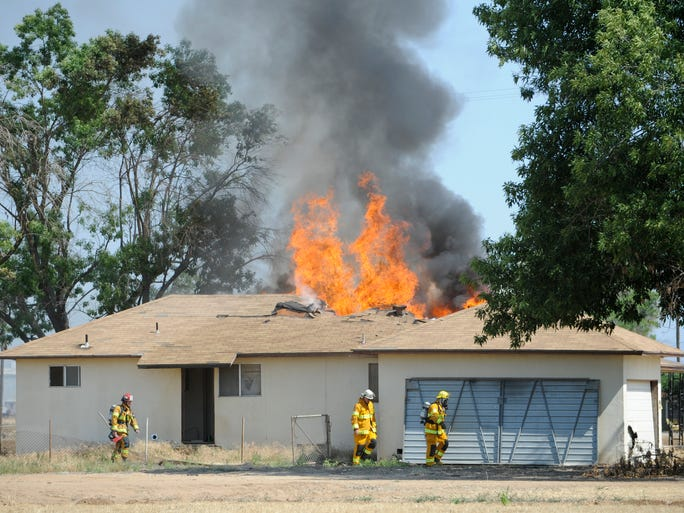 The Tulare County Fire Department works a house fire on the 36000 block of Road 124 north of Visalia on Friday. Battalion Chief Doug Hicks said the house was abandoned and no one was inside when firefighters arrived.