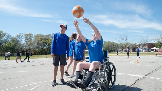 """Eighth-grader Emma O'Neill shoots a basketball after maneuvering through an obstacle course in a wheelchair during the annual Walk for SIMPACT event at Brown-Barge Middle School in Pensacola on Friday, March 23, 2018.  Emma's group, which was raising money for the Special Olympics, ran a booth called """"Take a Walk in Their Shoes"""".  They had various tasks like this wheelchair course for able bodied people to experience what those with special needs encounter in daily life."""