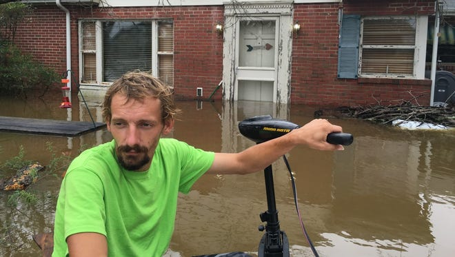 """George Griffin III uses an electric motor and a small boat to navigate through the backyards of homes on Middle Neck Lane on Friday after flooding of Middle Neck Branch. """"It's going to get worse,"""" he said."""