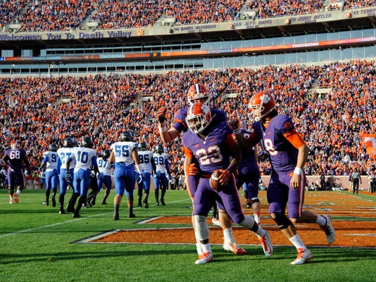 Clemson running back Tyshon Dye (23) celebrates scoring a touchdown with quarterback Cole Stoudt (18) and teammates during the first half of an NCAA college football game against Georgia State, Saturday, Nov. 22, 2014, in Clemson, S.C. (AP Photo/Rainier Ehrhardt)