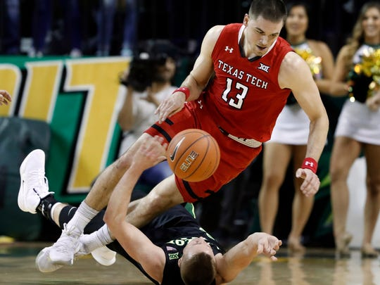 CORRECTS DATELINE TO WACO, NOT DALLAS - Texas Tech's Matt Mooney (13) falls over Baylor's Makai Mason, bottom, as the two scrambled for a loose ball in the first half of an NCAA college basketball game, Saturday, Jan. 19, 2019, in Waco, Texas. (AP Photo/Tony Gutierrez)