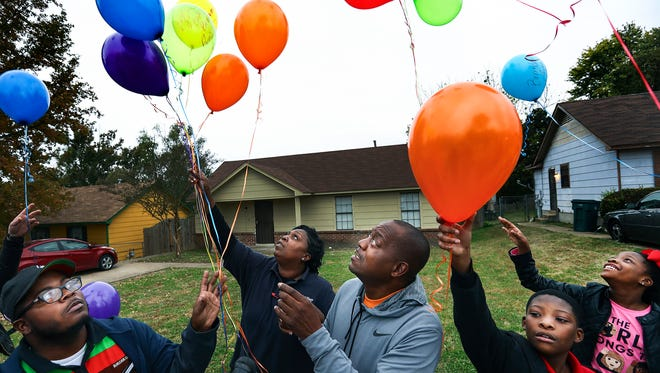 "Local peace activist, Reginald Johnson (middle) along with family and friends releases balloons in memory of his son Samuel ""Lil' Sam"" Johnson, who was shot and killed in 2014 on Halloween night."