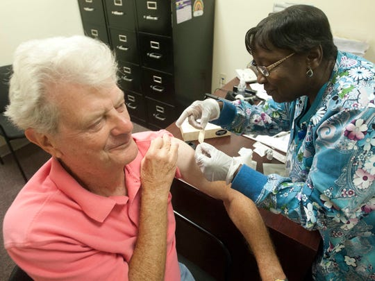 Ernest Crouch gets a band-aid applied from Louisville Public Health registered nurse Jean Hightower after she gave Crouch a high-dose flu shot Oct. 9, 2013.