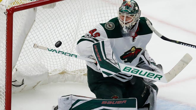 Minnesota Wild's Devan Dubnyk makes a save against the Chicago Blackhawks during the third period of an NHL hockey game Thursday, Oct. 12, in Chicago.