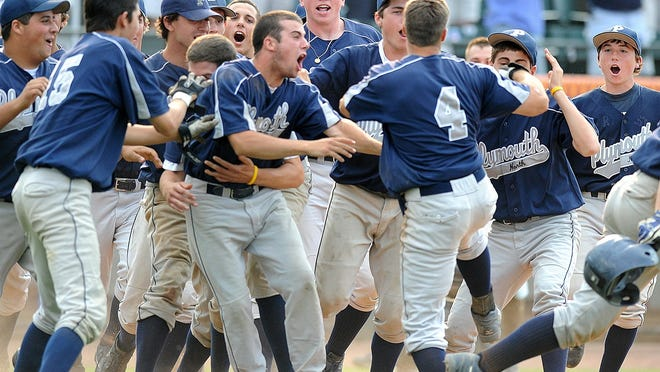Jared Canney (4) is greeted by teammates after scoring the winning run in extra innings for Plymouth North in its 2008 state title win over Auburn.