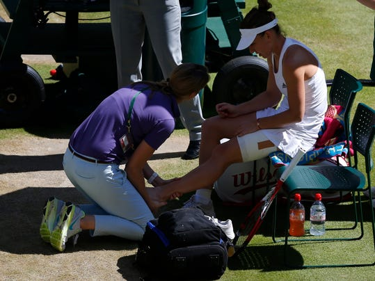 Simona Halep of Romania receives treatment on her ankle during the women's singles semifinal match against Eugenie Bouchard of Canada at the All England Lawn Tennis Championships in Wimbledon, London, Thursday, July 3, 2014. (AP Photo/Sang Tan, Pool)