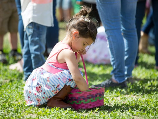 Ella Cortez, 3, looks in her Easter egg basket on Saturday,