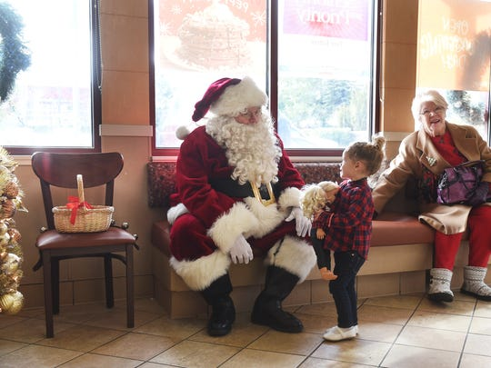 Reno local Bob Gailor plays Santa Claus and greets Emma Green as she goes for breakfast with her family to the International House of Pancakes in Spanish Springs on Dec. 23, 2016. Gailor has been donning the Santa suit for the past 50 years, and his father did the same for 66 holiday seasons.