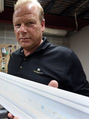 Energy Bank founder and CEO Neal Verfuerth poses for a photo with the light source convergent kit on Wednesday, July 13. The convergent kit could cut energy usage by 80 percent by converting traditional fluorescent lights to LED.