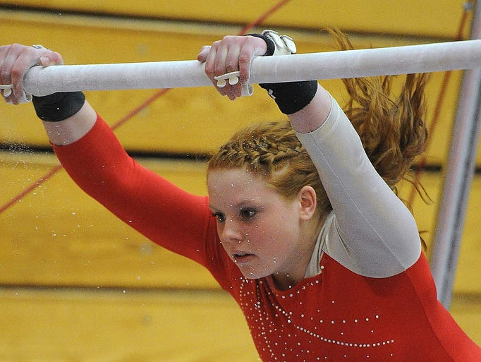 New Palestine's Kate Fee competes on the uneven bars. IHSAA Regional Gymnastics Championships were held at Columbus East High School Friday March 14, 2014.