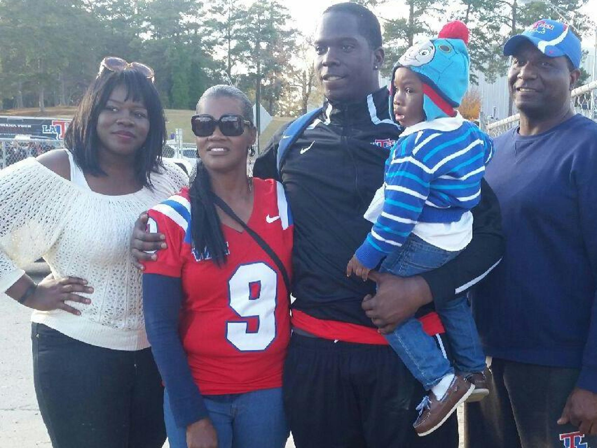 Vernon Butler, center, poses for a photo with his family