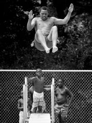 William Mac, 16, of West Nashville, demonstrates his diving technique to onlookers at the Hadley Park public swimming pool July 3, 1988.