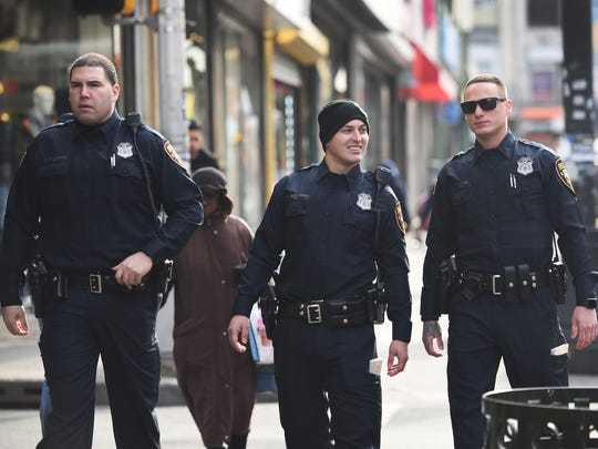 Three Paterson police officers, from left, Salvador Brancato, Ferdi Abedinoski and Edward J. Akins, who graduated from the Police Academy last week, walk the streets during their patrols for the first time in downtown Paterson on Tuesday.