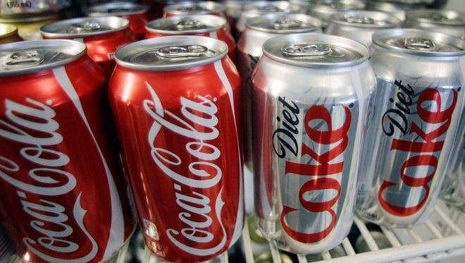 This file photo taken in 2011 shows cans of Coca-Cola and Diet Coke in a cooler at Anne's Deli in Portland, Ore.