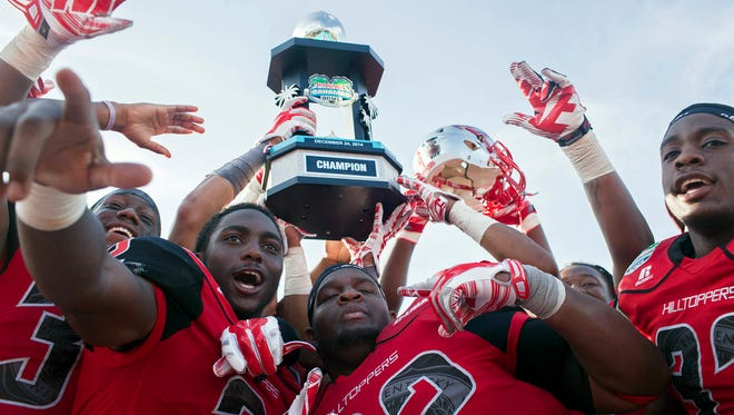 Western Kentucky football players hold up the trophy after their 49-48 victory over Central Michigan in the Bahamas Bowl NCAA college football game, Wednesday, Dec. 24, 2014, in Nassau, Bahamas. (AP Photo/The Daily News, Austin Anthony)