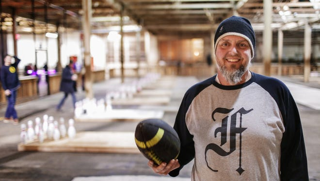 Chris Hutt, owner of The Fowling Warehouse in Hamtramck, poses for a photo on Friday December 19. The new nightlife spot incorporates the game where people use a football to knock down bowling pins in the large warehouse.