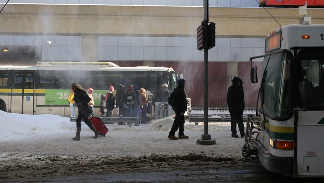 People arrive and wait for busses at the Rosa Parks Transit Center in downtown Detroit. Thursday, February 5,  2015.