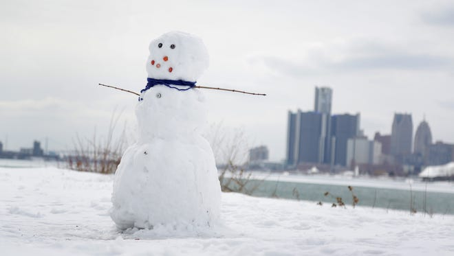 A lone snowman stand on the empty shores of the Detroit River on  Belle Isle in Detroit on Friday, Feb.  13, 2015.