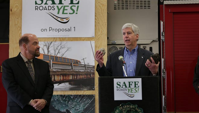 Michigan Governor Rick Snyder, right holds pieces of roads as Dearborn mayor Jack O' Reilly looks on during a press conference to urge voters to vote in favor of Proposal 1 to help fix Michigan roads during a press conference at Dearborn Fire Station 2 in Dearborn on Thursday, March 19, 2015.