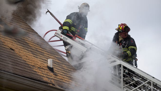 Firefighters from a dozen IFD vehicles work to contain an apartment fire at the corner of South East Street and East Iowa Street, Indianapolis, Friday, March 27, 2015. The blaze, which started in one of the three apartments and spread to the others, caused the evacuation from the building of two adults and three children, who were uninjured. A firefighter sustained a slight injury fighting the fire.