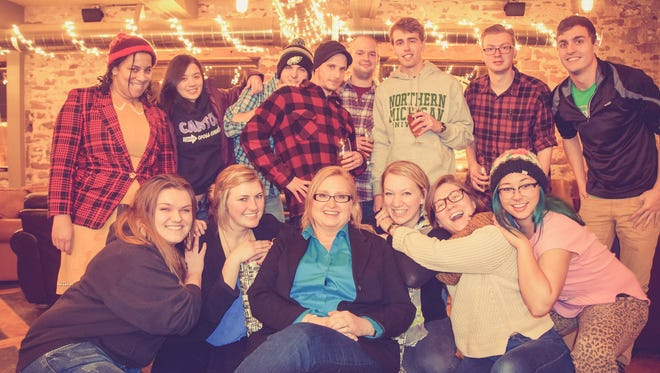Cheryl Reed, center, relaxes with the staff of the Northern Michigan University student newspaper at its Christmas party. Cheryl Reed was the faculty advisor to the student newspaper at Northern Michigan University. She is a veteran Chicago Sun-Times investigative reporter. The University relieved her of her advisory status in early April 2015.