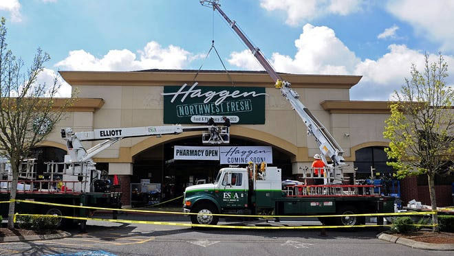 Workers prepare to hang the Haggen signage as the Albertsons grocery store transforms into Haggen, on Wednesday, April 1, in Tigard.