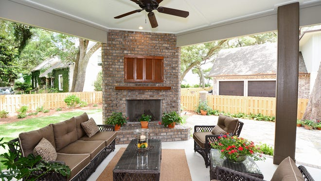 The Spragues entertain during summer or winter on the rear porch with a fireplace.