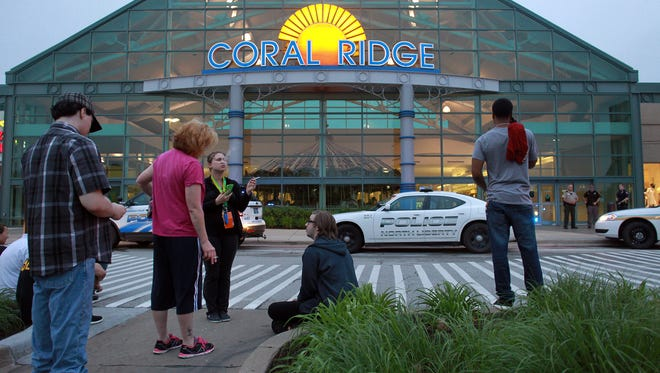 Shoppers and employees wait outside the Coral Ridge Mall following a shooting on Friday, June 12, 2015.