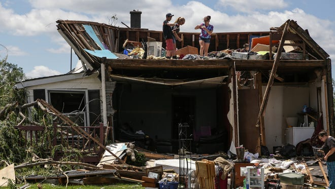 A family goes through their home on Tuesday June 23, 2015, that had the front and roof ripped off on Bray Road in Millington following a tornado that came through the area Monday evening.