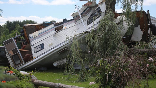A flipped camper stuck in trees is seen at a home on Tuesday, June 23, 2015 on Bray Road in Millington.