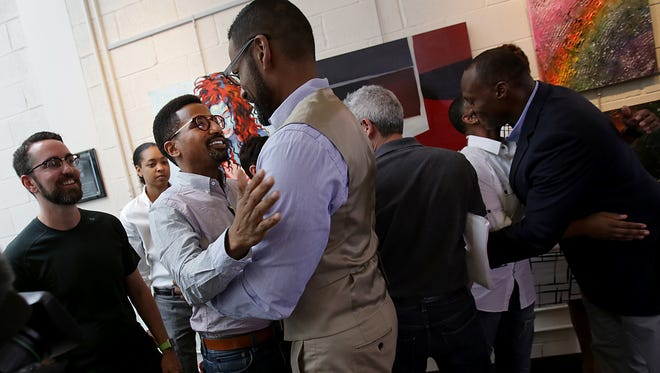 Darrious Hilmon, center, executive director of Affirmations, hugs Greg Hawkins, 40, of Detroit while his husband Zac Brandt, 39, of Detroit, left, looks on, during a press conference held at Affirmations in Ferndale, Mich.