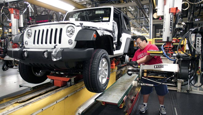 A worker installs tires on a 2014 Jeep Wrangler as it undergoes assembly at the Chrysler Toledo North Assembly Plant Jeep May 7, 2014 in Toledo, Ohio. i