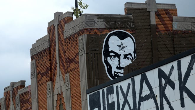 An Obey stencil hangs on the corner of Lakewood St. and E. Jefferson in Detroit on Tuesday, July 14, 2015. Internationally renowned graffiti artist, Shepard Fairey, is accused of causing about $9,000 in damage to nine illegally tagged properties while he was in Detroit last May.