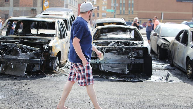 An onlooker walks through a parking lot at Beaubien and Gratiot in downtown Detroit where cars caught on fire while their owners were at a Tigers baseball game Sunday, July 19, 2015.