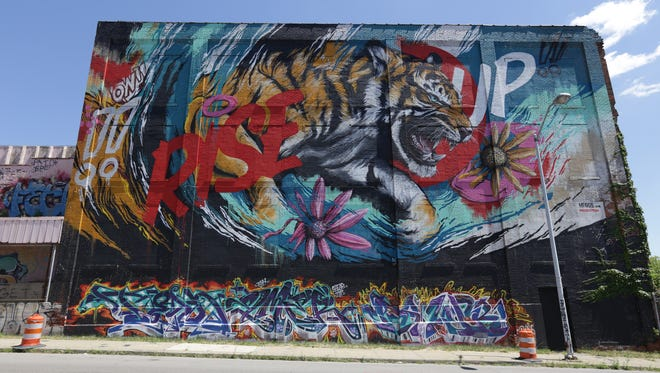 """""""Rise Up,"""" a mural by Meggs, on Russell Street on July 30, 2015. Meggs incorporated existing art (on the bottom of the wall) into his piece."""