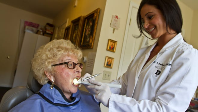 Dr. Lindsay Rubin of Dental Home Services gives a routine exam to Ann Fallon, a resident of Sunrise Assisted Living in Middletown.