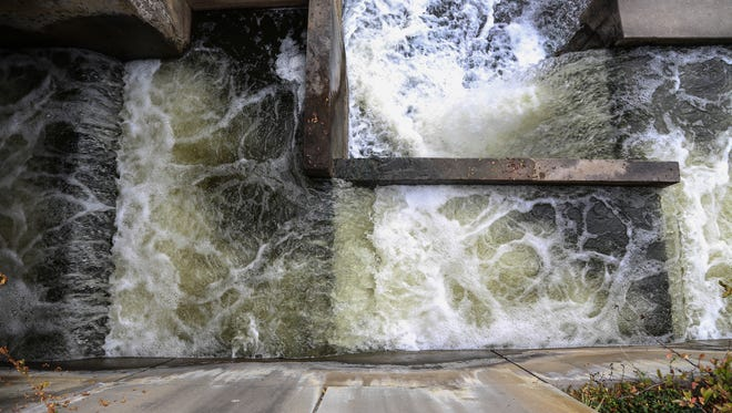Water from the Flint River is cascades down a section of the Hamilton Dam in downtown Flint last week.