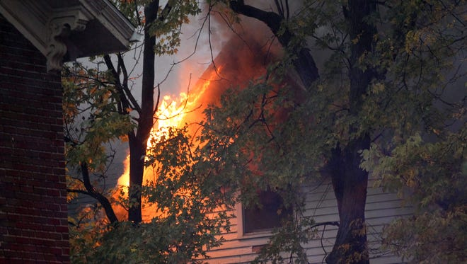 A house on College Street is seen burning on Tuesday, Oct. 20, 2015.