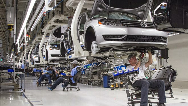 FILE - In this July 12, 2013, file photo, employees at the Volkswagen plant in Chattanooga work on the assembly of a Passat sedan.