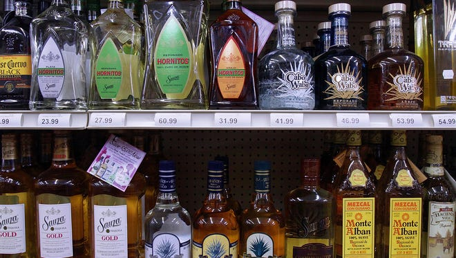 Bottles of alcohol line the shelves of a liquor store.