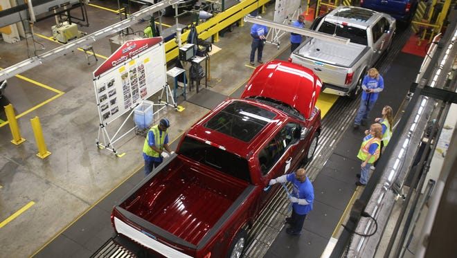 Workers inspect and go over the brand new 2015 F-150 as processes down the line at the Dearborn Truck Plant at the Ford Rouge Center on Tuesday, Nov. 11, 2014.