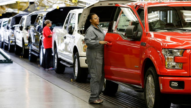 Workers inspect a new 2015 aluminum-alloy body Ford F-150 truck at the company's Kansas City Assembly Plant Friday, March 13, 2015, in Claycomo, Mo. Ford began production of the truck at the plant today after spending more than $1 billion in upgrades at the facility in preparation for the new vehicle. (AP Photo/Charlie Riedel)