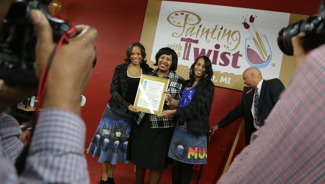 """Painting with a Twist"" co owners Michelle Lewis, left and her sister Donna Lewis, right pose for a photograph with Detroit city council president Brenda Jones."