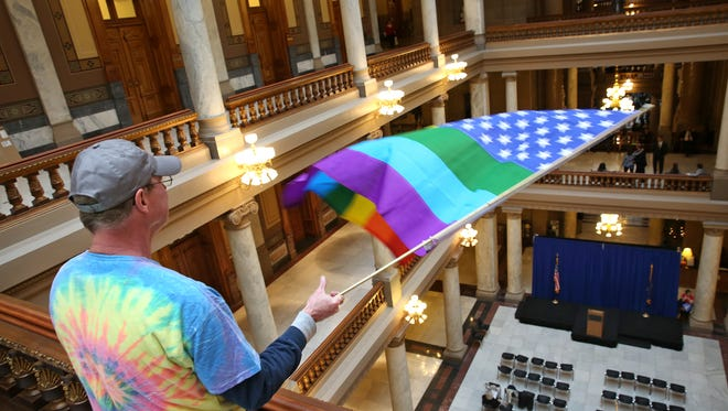 Mark Maudlin waved a rainbow flag over the banister from the fourth floor of the Statehouse hallways after a Freedom Indiana rally Nov. 17, 2015. Two floors below, there had been a prayer rally earlier, with opposing views, sponsored by the Indiana Pastors Alliance.