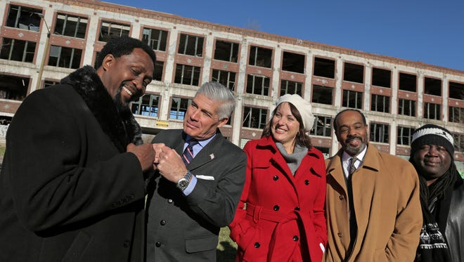 Former boxing champion Thomas (Hitman) Hearns fist-bumps with Packard Plant developer Fernando Palazuelo at the Detroit plant Friday. With them are, from left, Kari Smith, Harley K. Brown and Gregory Johnson.